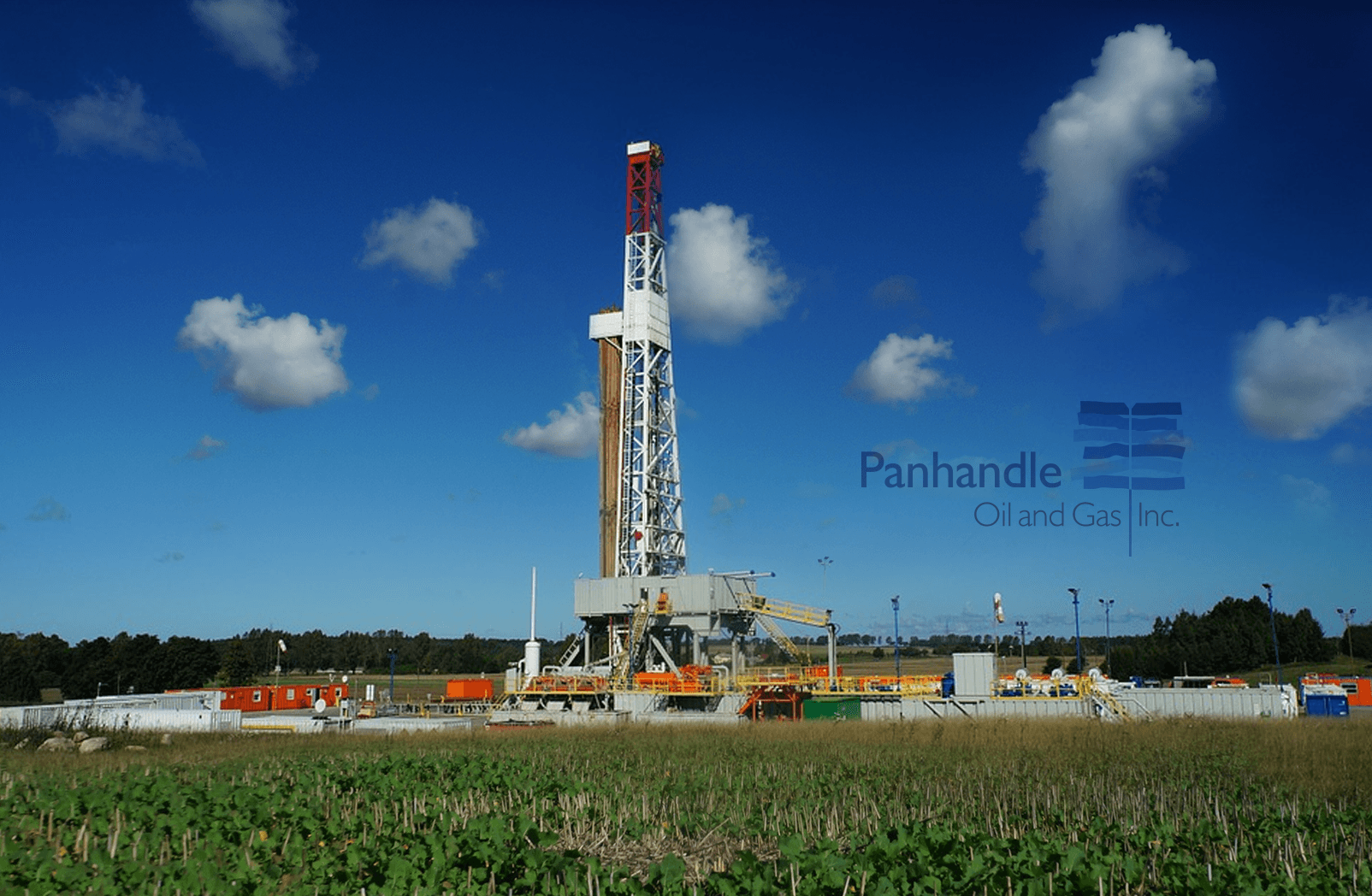 View of oil field rig on a beautiful day with Panhandle Oil and Gas Inc. Logo